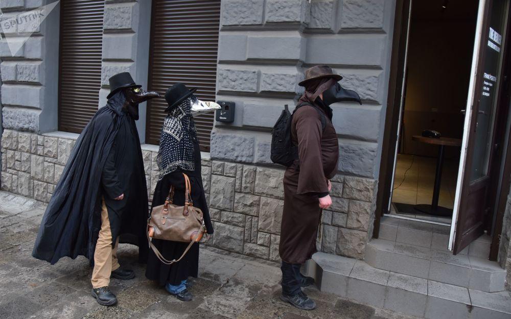 People wearing plague doctor masks walk on a street, amid an outbreak of the coronavirus disease, in Lviv, Ukraine.