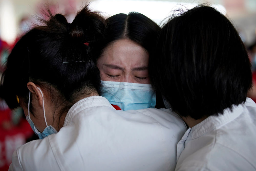 Medical workers hug at the Wuhan Tianhe International Airport after travel restrictions to leave Wuhan, the capital of Hubei province and China's epicentre of the novel coronavirus disease (COVID-19) outbreak, were lifted, April 8, 2020.