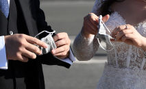 Молодожены с медицинскими масками в руках, иллюстративное фото
