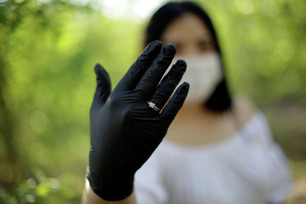 Мексиканская невеста в защитной маске и перчатках демонстрирует кольцо