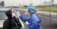 Врач делает анализ на коронавирус водителю мотоцикла на блокпосте