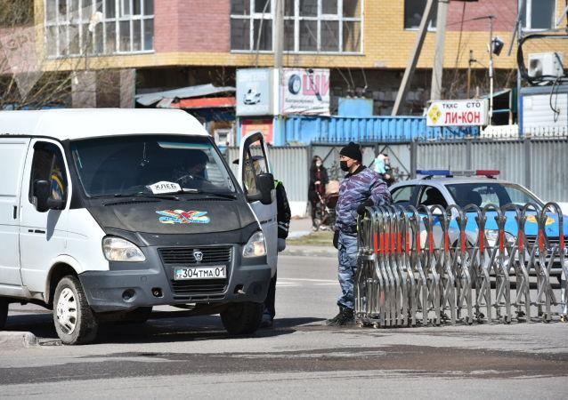 Сотрудник полиции у изолированного на карантин района в Нур-Султане
