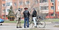 Азаматтармен сөйлесіп тұрған полицей