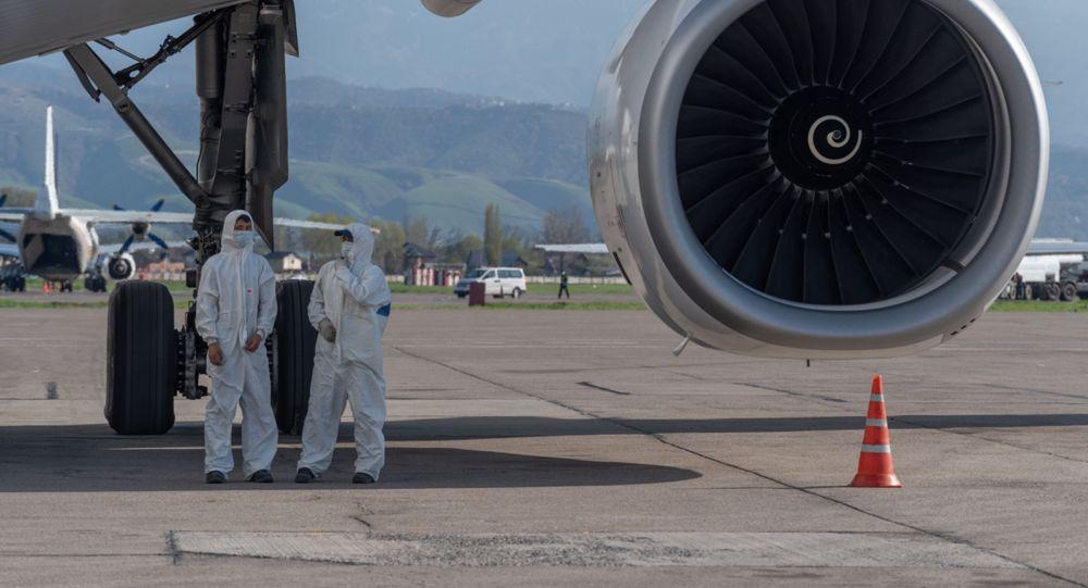 Сотрудники аэропорта Алматы под крылом самолета