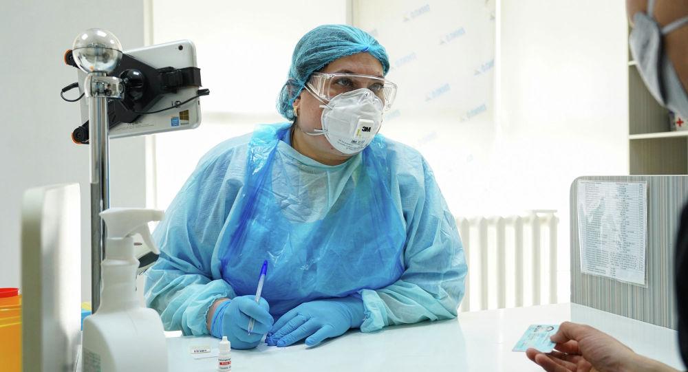 Дәрігер коронавирусқа тест тапсырғалы жатқан пациенттің мәліметтерін жазып жатыр