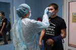 Врач измеряет температуру пациента перед анализом на коронавирус