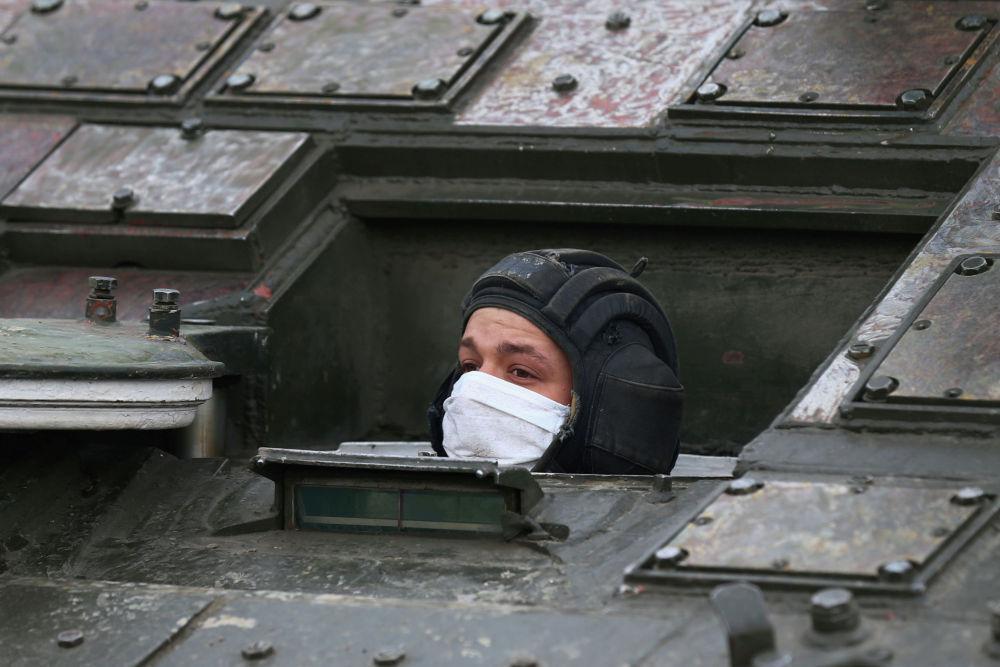 Танкист в защитной маске в люке во время репетиции парада Победы