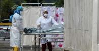 Сотрудники больницы вывозят скончавшегося от коронавируса
