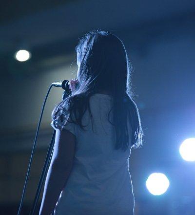 Девочка исполняет песню на сцене