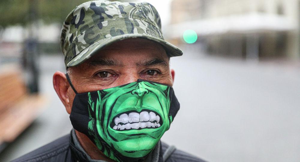 Мужчина в маске с изображением Халка на улице