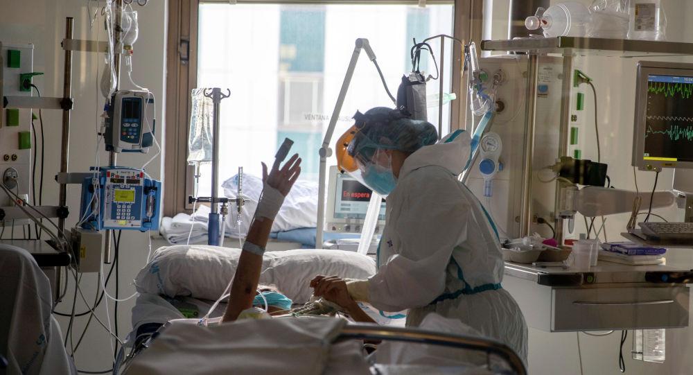 Медик поддерживает пациента в палате интенсивной терапии в больнице с коронавирусом