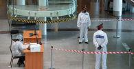 Полицейские в защитных костюмах в аэропорту Нур-Султана