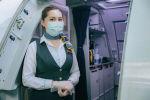 Стюардесса авиакомпании Air Astana встречает пассажиров