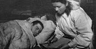 Сестра медсанбата пишет письмо родным под диктовку раненого солдата