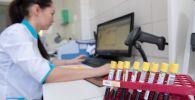 Сотрудница лаборатории изучает результаты анализов на коронавирус
