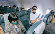 Пассажиры в масках на борту самолета
