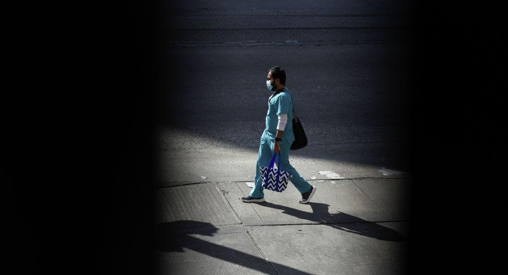 Медик в защитной  маске идет по двору больницы с коронавирусом