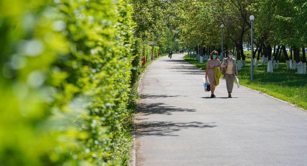 Девушки в масках прогуливаются по улицам Нур-Султана после снятия режима ЧП люди парк дорога казахстанцы весна зелень