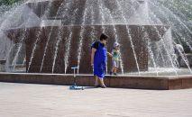 Женщина в маске гуляет с ребенком у фонтана в Нур-Султане