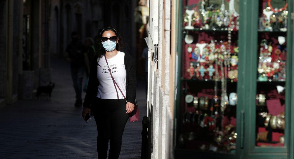 Девушка в маске прогуливается у магазина сувениров