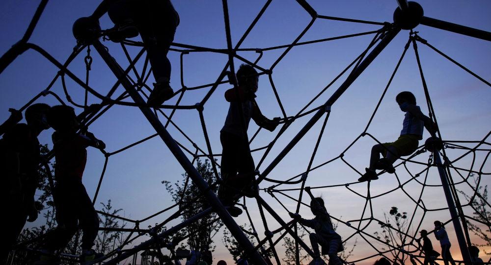 Дети играют на спортивной площадке вечером