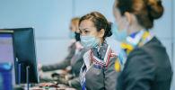 Сотрудницы авиакомпании Air Astana регистрируют пассажиров в аэропорту Алматы