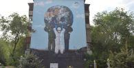 Граффити изображает медика, полицейского и военного, которые вместе держат в руках земной шар