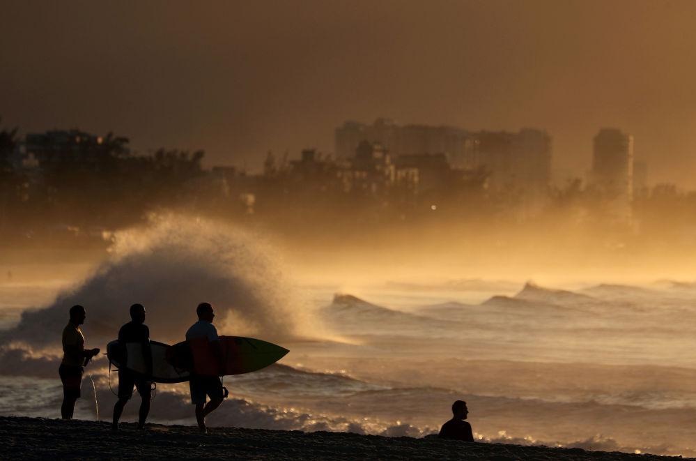 Surfers walk during a sunrise at Recreio dos Bandeirantes beach, amid the coronavirus disease (COVID-19) outbreak, in Rio de Janeiro, Brazil April 25, 2020.