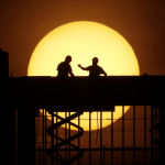 Workers are silhouetted against the rising sun as they toil on a new apartment building in Kansas City, Mo. Wednesday, April 8, 2020. Construction workers are among the people exempt from the city's stay-at-home order which remains in effect in an effort to slow the spread of the new coronavirus.