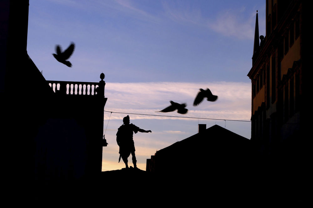 Pigeons fly over the Augustus fountain on the town hall square shortly before sunrise in Augsburg, Germany, Thursday, April 16, 2020.