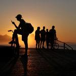 People are seen during a sunrise at Recreio dos Bandeirantes beach, amid the coronavirus disease (COVID-19) outbreak, in Rio de Janeiro, Brazil April 25, 2020.