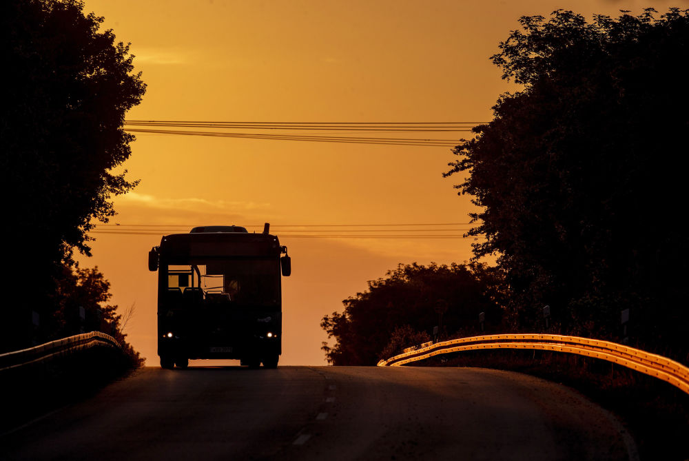 An empty bus comes along a land road in Frankfurt, Germany, as the sun rises Wednesday, May 13, 2020.