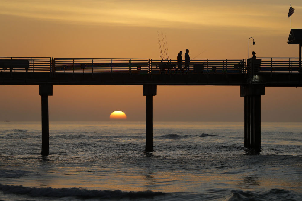 People walk on a pier with their fishing poles during sunrise on the Gulf of Mexico, in Orange Beach, Ala., Friday, March 13, 2020.
