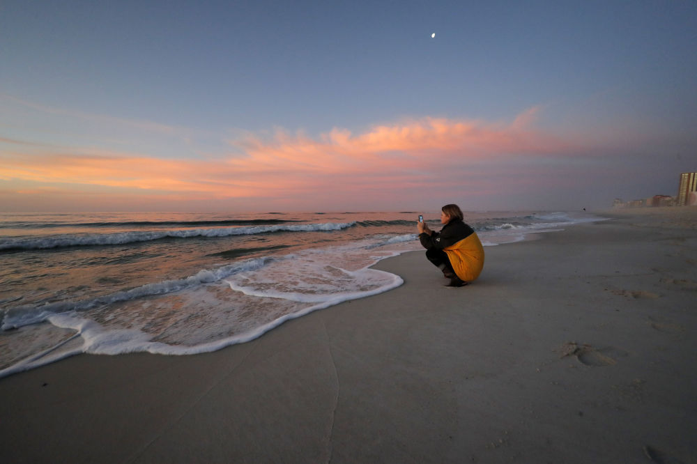File - In this March 13, 2020, file photo, Rachel Bobo, of Orange Beach, Ala., takes photos of the sunrise on the Gulf of Mexico in Gulf Shores, Ala. The spring of coronavirus feels a lot like the summer of oil to residents along the Gulf Coast. Bars and restaurants are empty in Florida because of an invisible threat nearly a decade after the BP oil spill ravaged the region from the ocean floor up, and condominium reservations have taken a nosedive in Alabama.