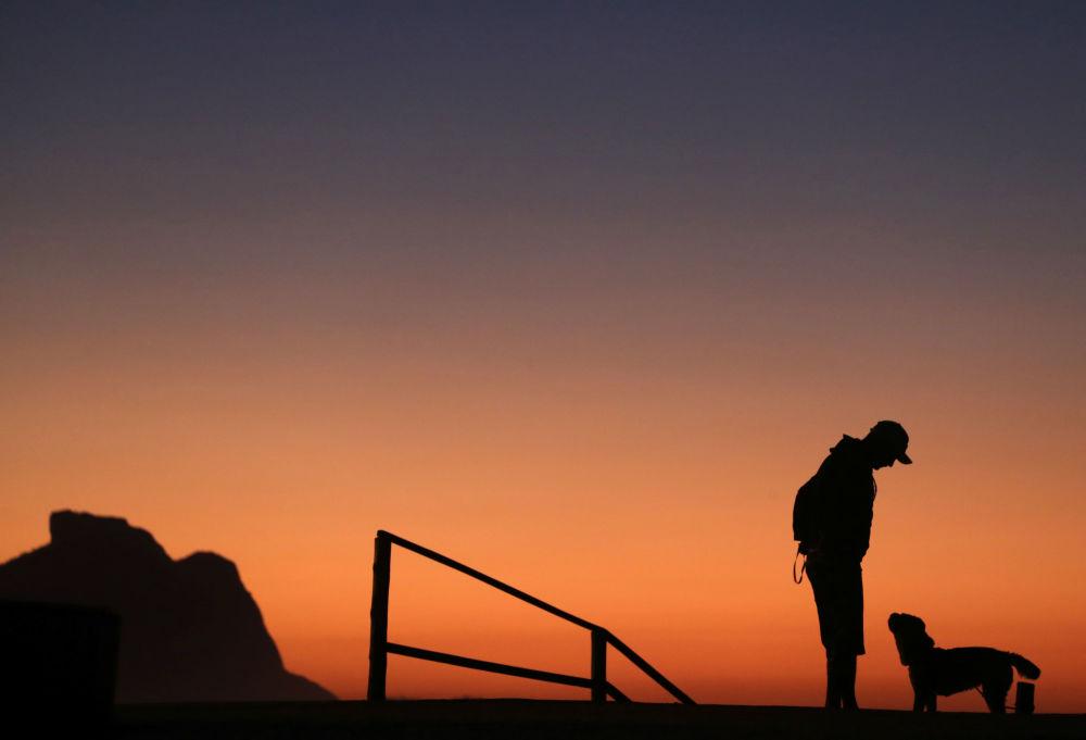A man and his dog are seen during a sunrise at Recreio dos Bandeirantes beach amid the coronavirus disease (COVID-19) outbreak, in Rio de Janeiro, Brazil April 25, 2020.