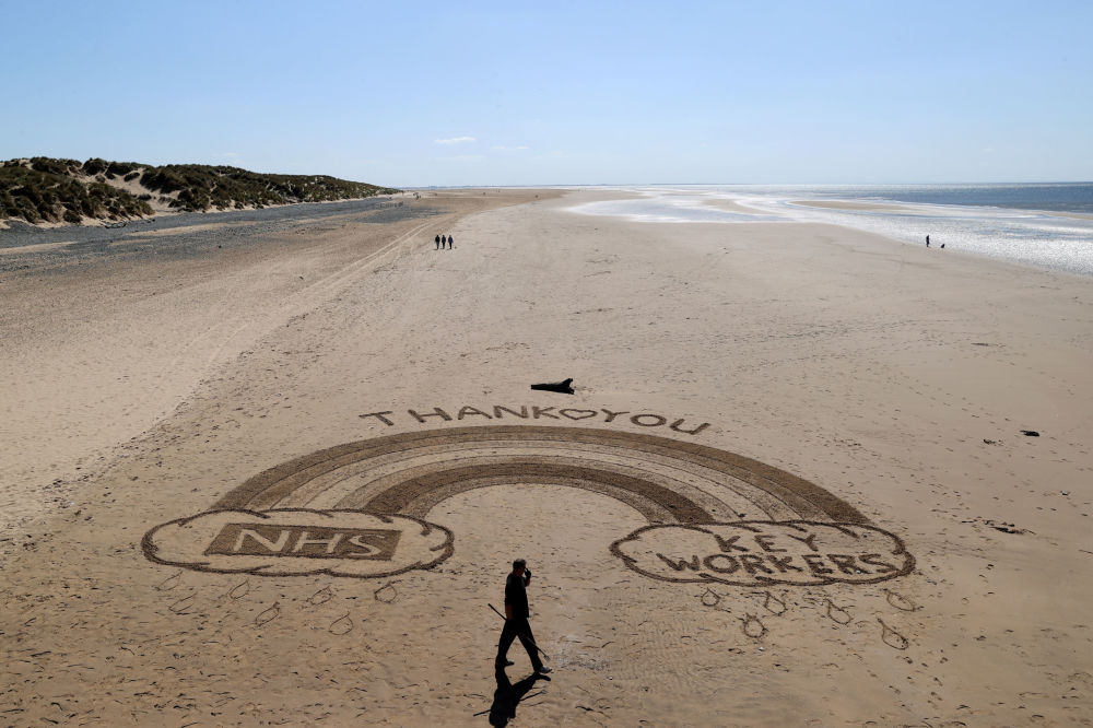 Ben from Sandymental art team works on a sand drawing in tribute to the NHS and Key workers on a beach in Lytham St Anne's, as the spread of the coronavirus disease (COVID-19) continues, Lytham St Anne's, Britain, April 20, 2020.