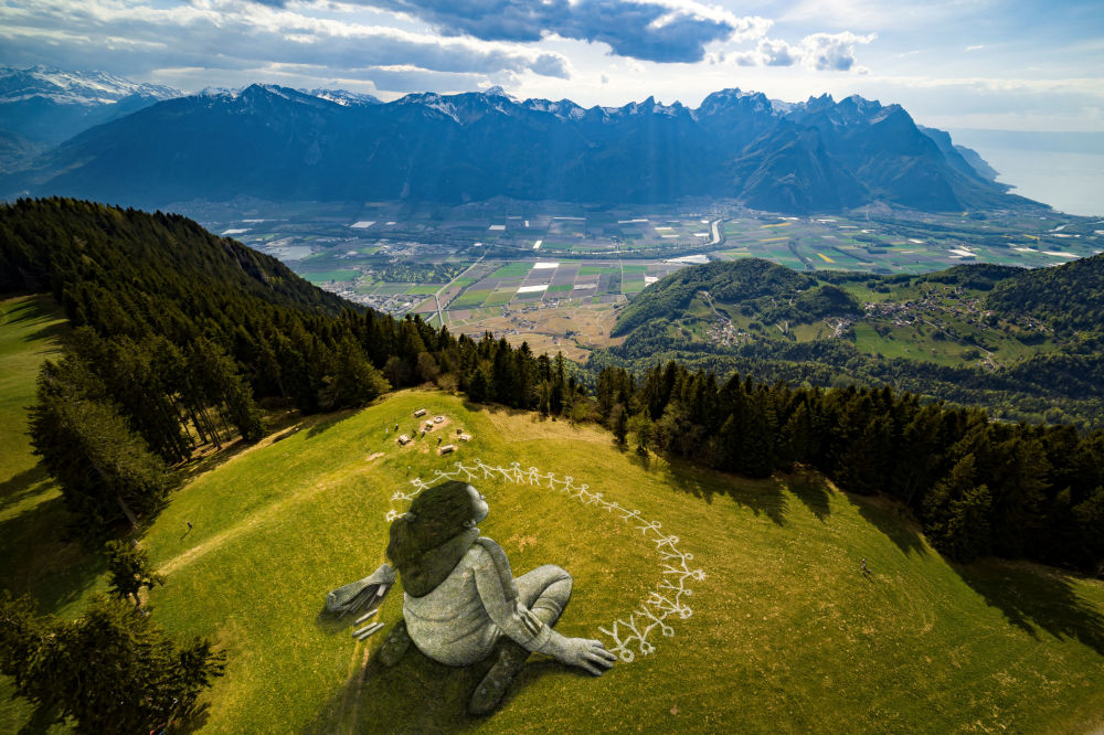 An artwork called Beyond Crisis by French artist Guillaume Legros aka Saype and created with an eco paint made out of chalk and coal over a 3000 sqm field is pictured during the coronavirus disease (COVID-19) outbreak in Leysin, Switzerland, April 24, 2020 in this picture obtained by Reuters April 26, 2020.