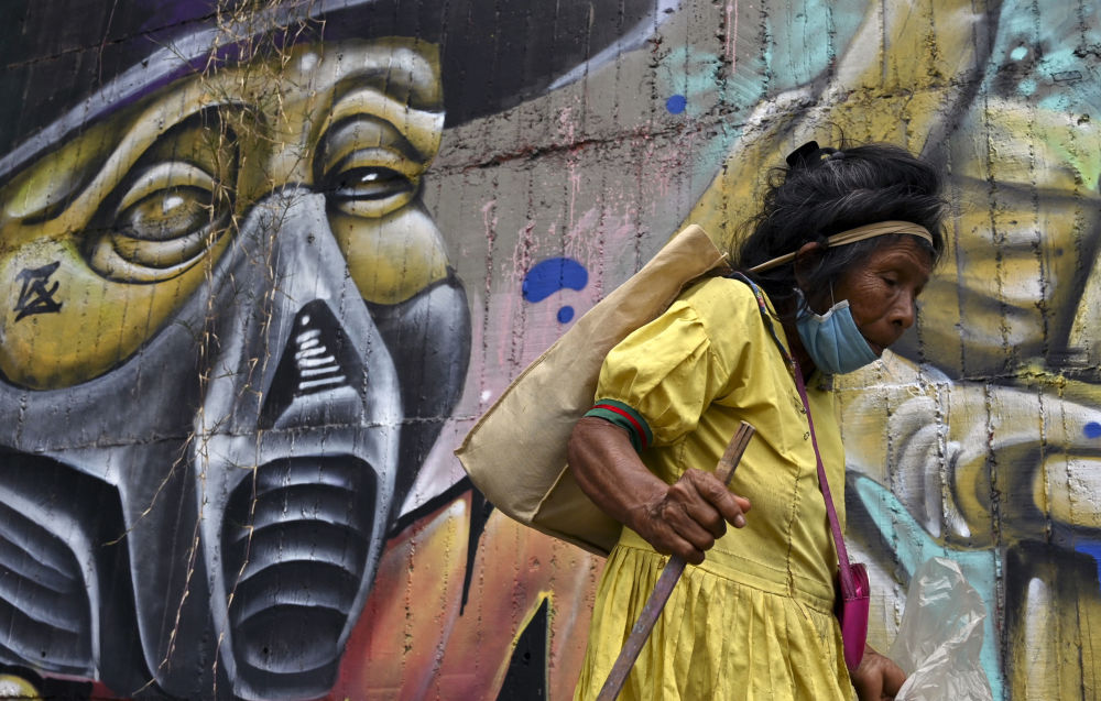A Colombian indigenous woman walks in front of a mural, in Cali, Colombia, on May 11, 2020.