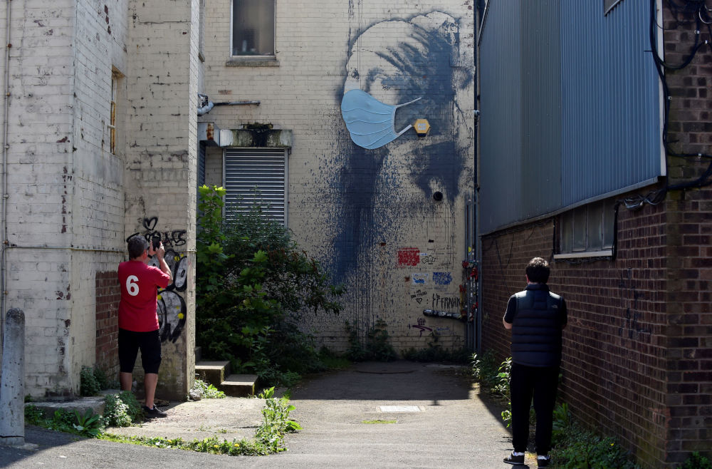 A man takes a picture of a piece of Banksy street art titled The Girl with the Pierced Eardrum, now adorned with a protective face mask, amid the spread of the coronavirus disease (COVID-19), at Albion Dock in Bristol, Britain April 23, 2020.