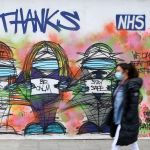 A pedestrian wearing PPE (personal protective equipment), including a face mask as a precautionary measure against COVID-19, walks past street art graffiti praising the workers od Britain's NHS (National Health Service) and other key workers, by artists Nathan Bowen and Harry Blackmore, in London on April 23, 2020. on May 13, 2020, as people start to return to work after COVID-19 lockdown restrictions were eased. - Britain's economy shrank two percent in the first three months of the year, rocked by the fallout from the coronavirus pandemic, official data showed Wednesday, with analysts predicting even worse to come. Prime Minister Boris Johnson began this week to relax some of lockdown measures in order to help the economy, despite the rising death toll, but he has also stressed that great caution is needed.