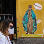 Women wearing a face mask walk past a mural by Art Flase depicting the Virgin Mary wearing a protective mask and saying Keep a distance in downtown Naples on May 13, 2020 during the country's lockdown aimed at curbing the spread of the COVID-19 infection, caused by the novel coronavirus.