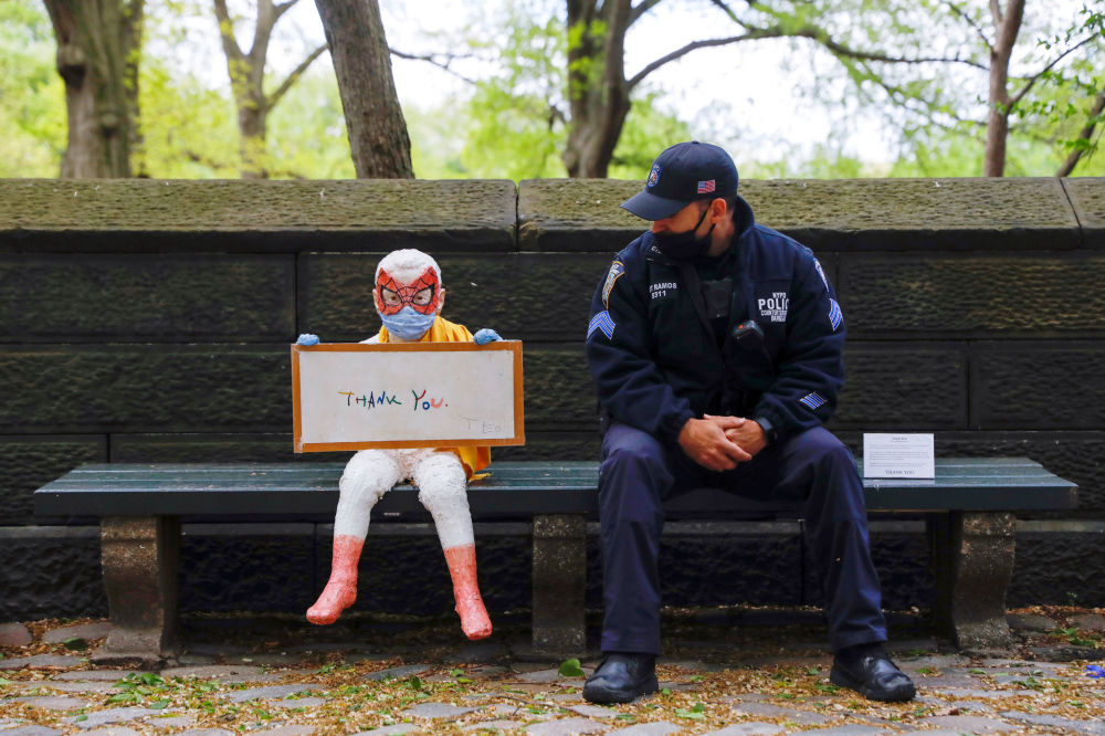 A New York City Police Department (NYPD) officer sits beside an art piece titled -ThAnK YoU- by Benat Iglesias Lopez and his four-year-old son Teo which was made to thank frontline workers, outside Central Park during the outbreak of the coronavirus disease (COVID-19) in the Manhattan borough of New York City, U.S., May 9, 2020.