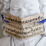 A bust of Bach with a face mask made of notes from the cantata My heart swims in blood is on display in the Bach Archive in front of the exhibition Bach and Beethoven in Leipzig, Germany, Tuesday, May 12, 2020. True art remains eternal. Actually, the show was supposed to start on March 26, but then coronavirus outbreak threw the plans overboard. From May 14 to October 18, 200 the exhibition shows the influence Bach's compositions had on Beethoven.