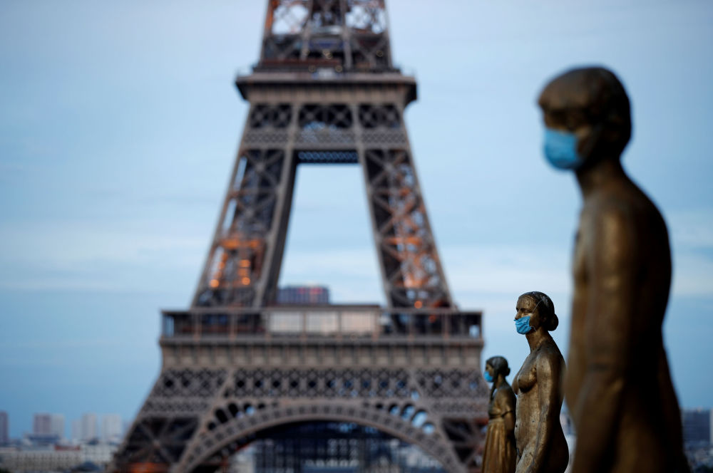 FILE PHOTO: Golden Statues at the Trocadero square near the Eiffel tower wear protective masks during the outbreak of the coronavirus disease (COVID-19) in Paris, France, May 2, 2020.