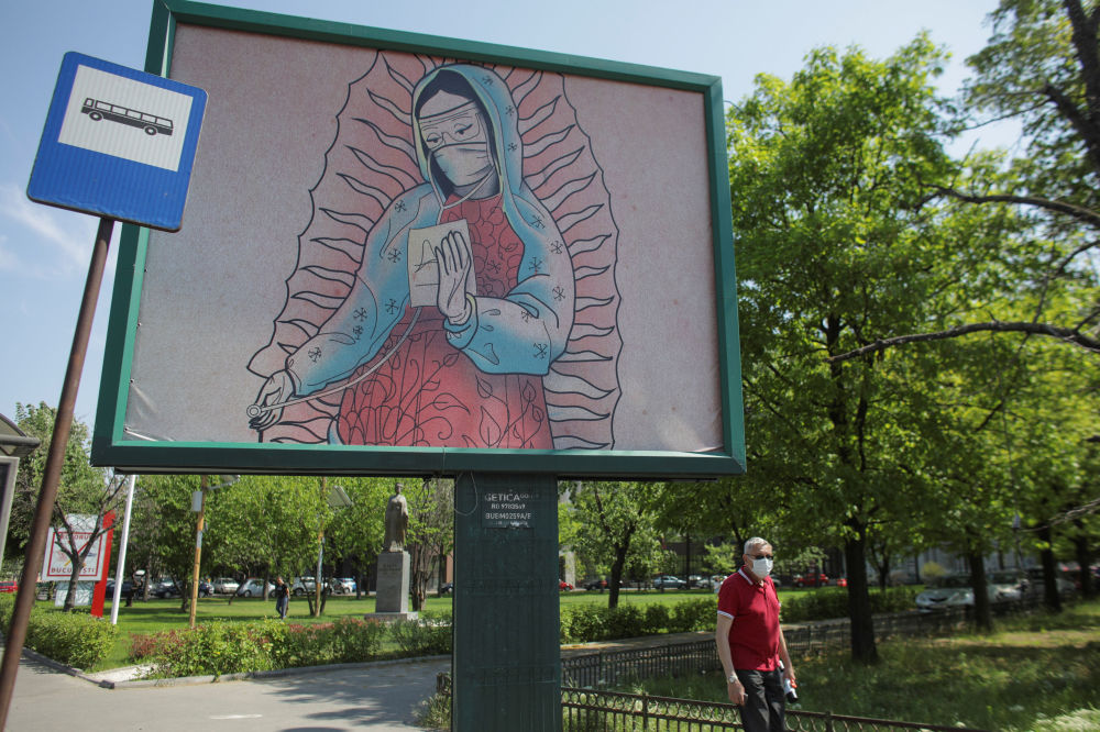 An outdoor poster shows a doctor depicted in a style similar to Latin American religious paintings, in Bucharest, Romania, April 29, 2020. The poster, created by Romanian illustrator Wanda Hutira, is part of a Thank you doctors campaign.