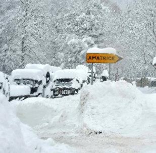 Человек идет во время сильного снегопада в Amatrice, после серии землетрясений в центральной части Италии, 18 января 2017 года