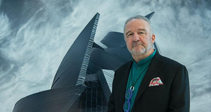 Жан Франсуа Розье на фоне своей картины, на которой ЦКЗ Казахстан
