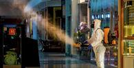 Человек в защитном костюме занимается санитарной обработкой в ТРЦ