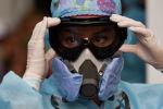 Девушка-медик поправляет защитные очки и респиратор в больнице с коронавирусом