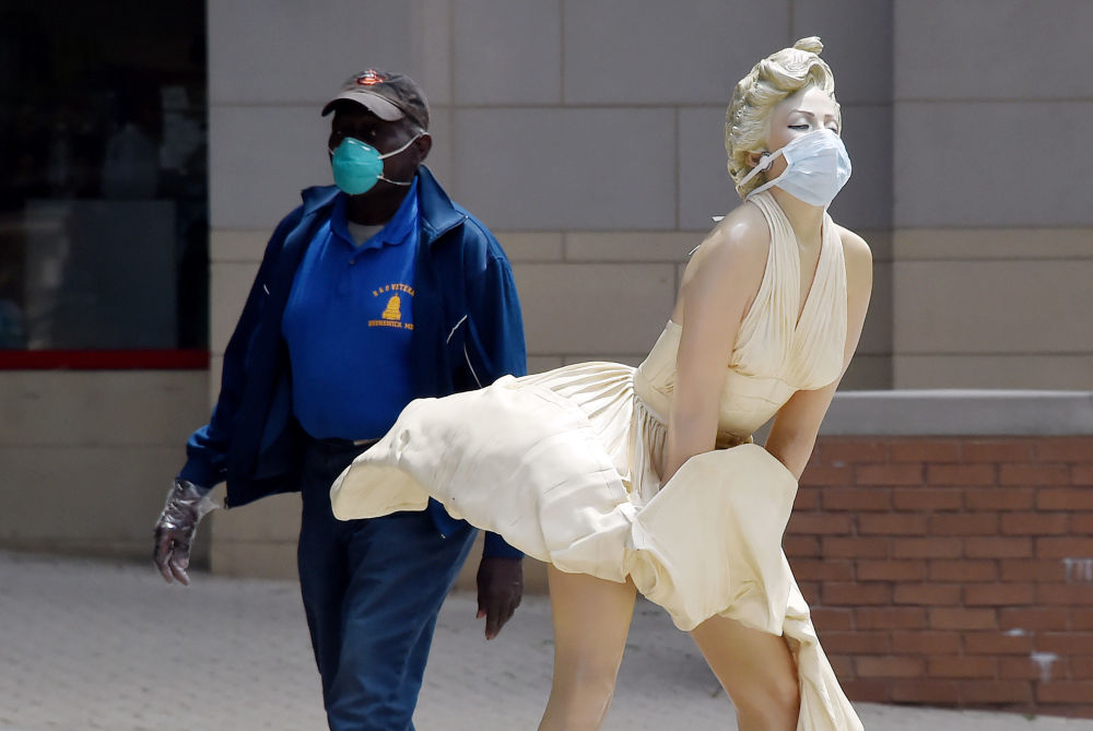A man wearing a face mask walks past The Forever Marilyn statue by Seward Johnson,  which is also wearing a mask amid the Coronavirus outbreak at National Harbor, Maryland  on May 11, 2020.